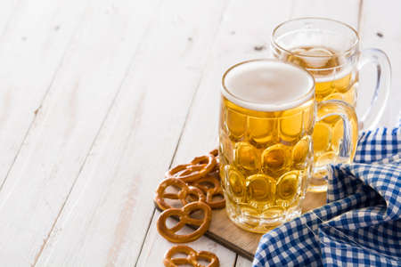 Oktoberfest beer in jar and pretzel on white wooden table. Copyspace