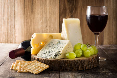 Assortment of cheeses and wine on wooden table Foto de archivo