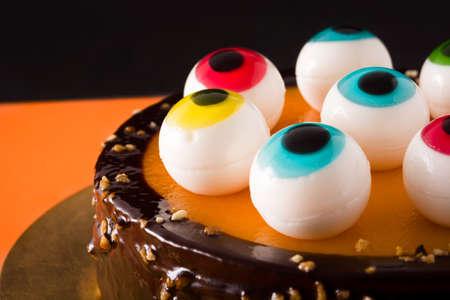 Halloween cake with candy eyes decoration on orange and black background. Close up