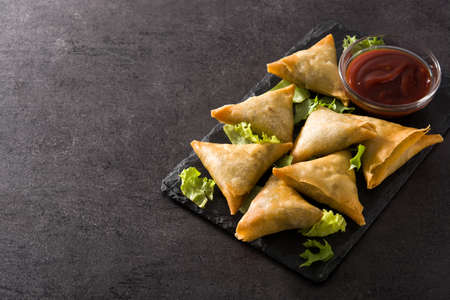 Samsa or samosas with meat and vegetables on black background. Traditional indian food. Copyspace