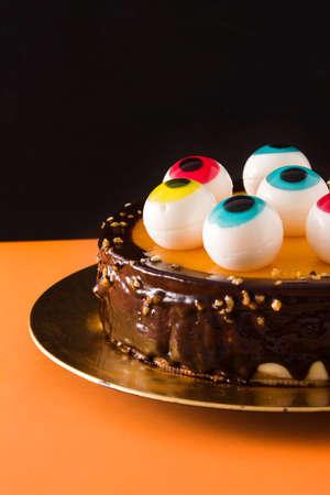 Halloween cake with candy eyes decoration on orange and black background.