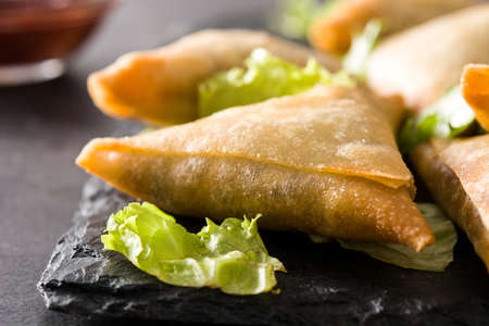 Samsa or samosas with meat and vegetables on black background. Traditional indian food. Close up