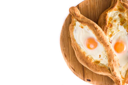 Traditional Adjarian Georgian khachapuri with cheese and egg isolated on white background. Top view. Copyspace Imagens