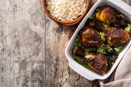 Roasted tandoori chicken with basmati rice on wooden table.Top view. Copyspace Imagens