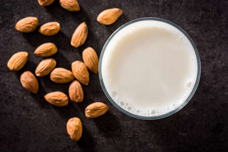 Almond milk in glass on black background. Top view