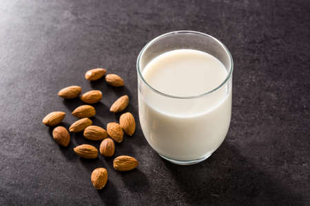 Almond milk in glass on black background