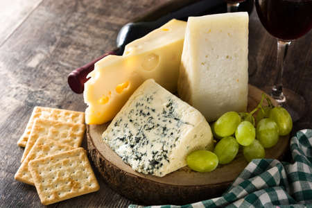Assortment of cheeses and wine on wooden table. Imagens