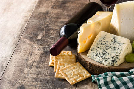 Assortment of cheeses and wine on wooden table. Copyspace