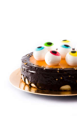 Halloween cake with candy eyes decoration on white background