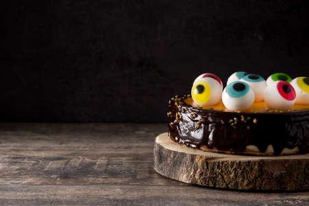 Pastel de Halloween con decoración de dulces en mesa de madera. Copia espacio Foto de archivo