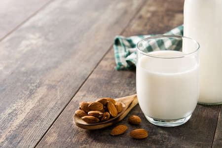 Almond milk in glass and bottle on wooden table. Copy space