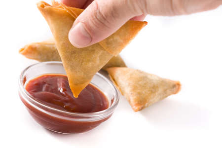 Hand with samosa dipping in sweet and sour sauce isolated on white background. Traditional Indian food