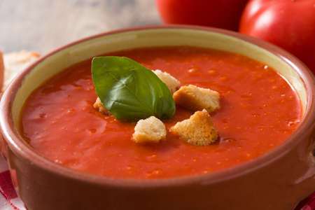 Tomato soup in brown bowl on wooden table. Close up