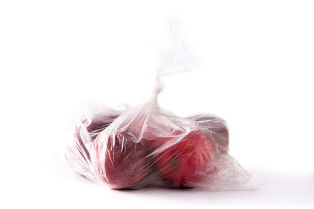 Red apples packaged in plastic bag isolated on white background