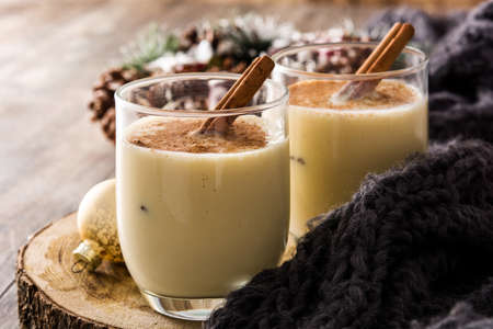 Homemade eggnog with cinnamon in glass on wooden table. Typical Christmas dessert.