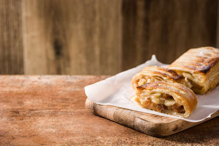 Traditional homemade apple strudel on brown background. Copy space