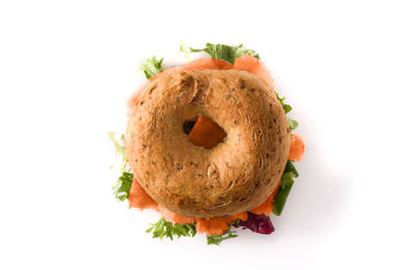 Bagel sandwich with cream cheese, smoked salmon and vegetables isolated on white background. Top view Imagens
