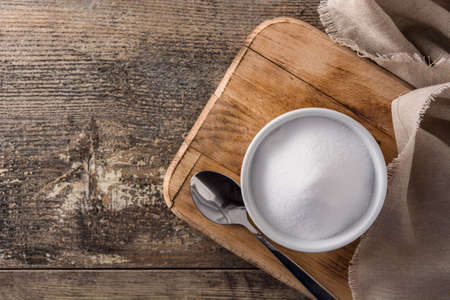 Baking soda in white bowl on wooden table.Top view. Copy space Stok Fotoğraf