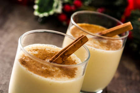 Homemade eggnog with cinnamon in glass on wooden table. Typical Christmas dessert. Zdjęcie Seryjne