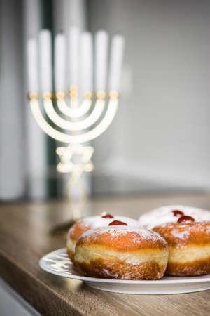 Jewish Hanukkah menorah and sufganiyot donuts on wooden table Stock Photo