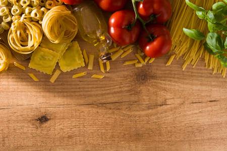 Italian pasta and ingredients. Ravioli, penne pasta, spaghetti, tortellini, tomatoes and basil on wooden table