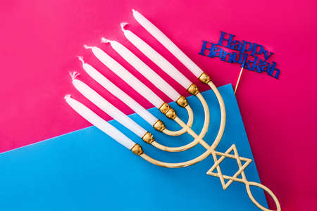 Jewish Hanukkah menorah on blue and pink background