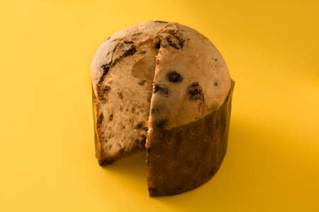 Christmas chocolate panettone cake isolated on yellow background. Stock Photo
