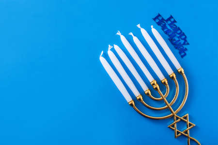 Jewish Hanukkah menorah on blue background. Top view Copy space