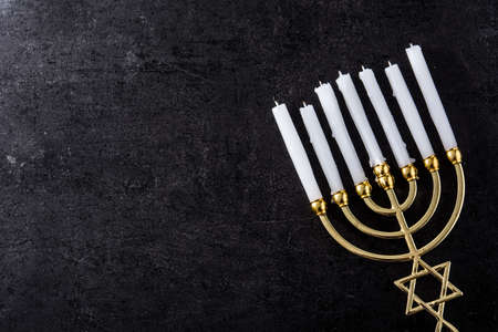 Jewish Hanukkah menorah on black background. Copy space