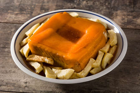 Typical Portuguese francesinha sandwich with french fries on wooden table