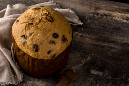 Christmas chocolate panettone cake on wooden table. Copy space