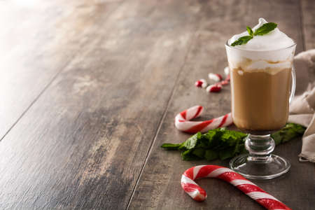 Peppermint coffee mocha for Christmas on wooden table. Copy space