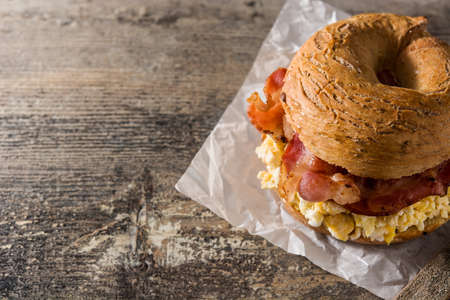 Bagel sandwich with bacon, egg and cheese on wooden table. Copy space 版權商用圖片