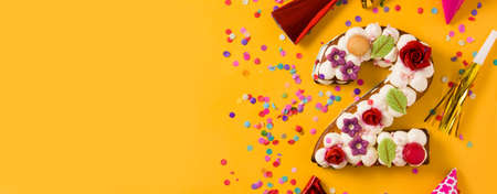 Number two cake decorated with flowers, macarons and confetti isolated on yellow background