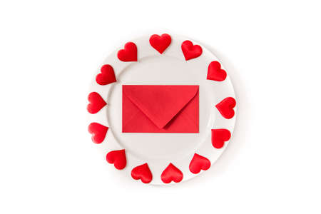 White plate surrounded by hearts and paper envelope on white background