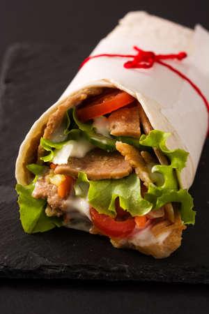 Doner kebab or shawarma sandwich on black slate background. Close up