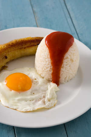 Cuban rice Typical Cuban rice with fried banana and fried egg on a plate on wooden table.