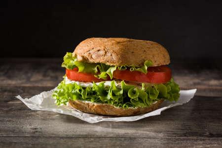 Gemüse-Bagel-Sandwich mit Tomaten, Salat und Mozzarella-Käse auf Holztisch.