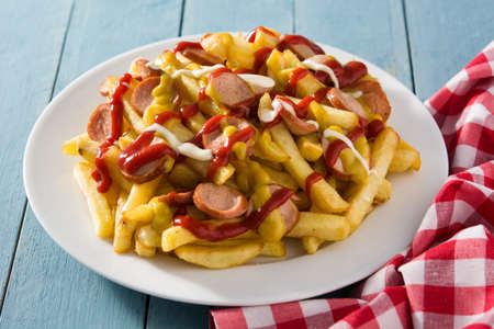 Typical Latin America Salchipapa. Sausages with fries, ketchup, mayo and mustard. Reklamní fotografie