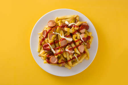 Typical Latin America Salchipapa on yellow background. Sausages with fries, ketchup, mayo and mustard.