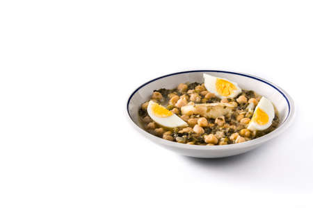 Chickpea stew with spinach and cod or potaje de vigilia isolated on white background