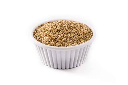 Golden flax seeds in white bowl isolated on white background