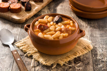 Typical Spanish fabada asturiana in crockpot on wooden table