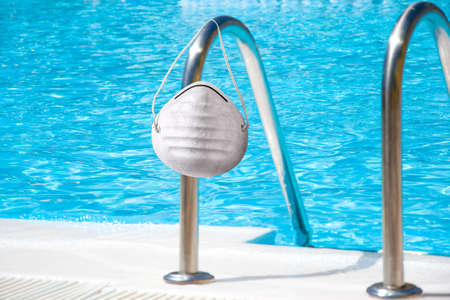 Swimming pool and medical protective mask on summer during coronavirus COVID-19