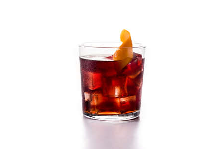 Boulevardier cocktail and orange zest in glass isolated on white background