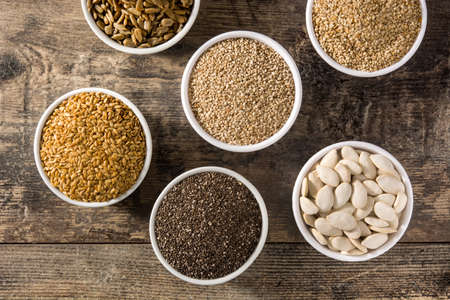 Assortment of different seeds in bowl on wooden table. Pumpkin, linen, chia, sunflower and sesame seeds. Archivio Fotografico