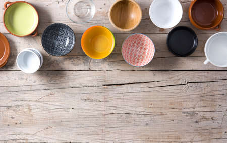 Set of different empty bowls on wooden background