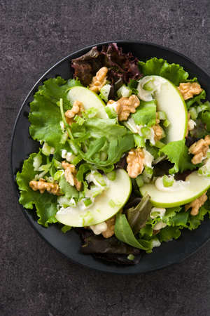 Fresh Waldorf salad with lettuce, green apples, walnuts and celery on black slate background