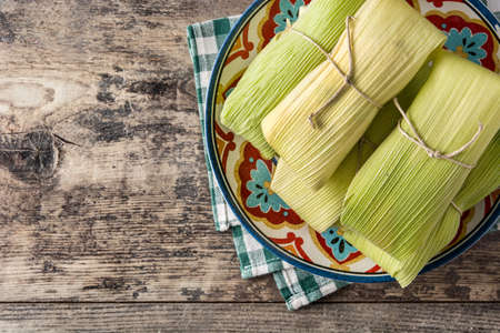 Mexican corn and chicken tamales on wooden table Stock Photo