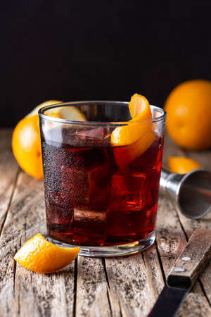 Boulevardier cocktail and orange zest on wooden background